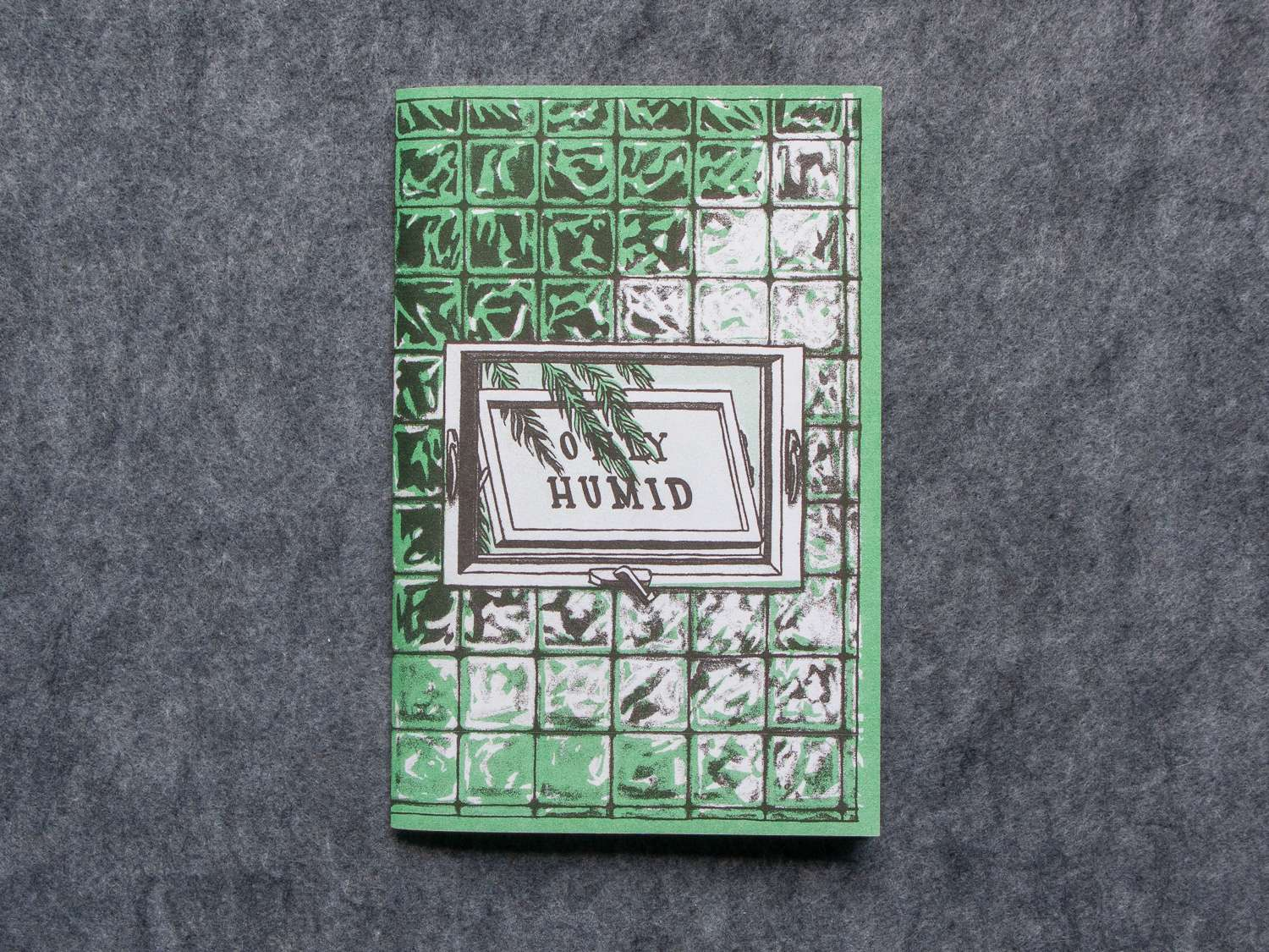 """Only Humid"" risograph zine front cover showing a tiled glass wall with a window displaying the title"